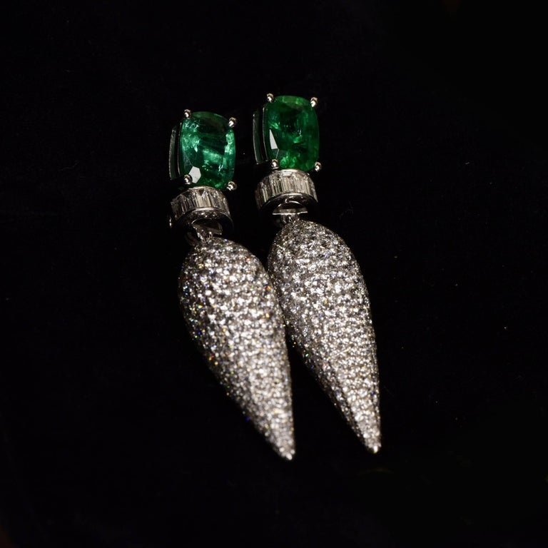 Icicle motif dangler earrings with unenhanced emerald and round brilliant diamonds. This dramatic earring features an icicle of pave diamonds hanging from the ear that dazzles with its stunning play of light. The captivating earrings boldly blend