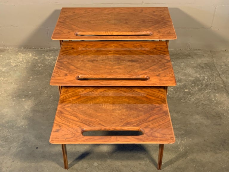 A rare set of three nesting tables with handle cutout and tapering legs. Designed by Ico Parisi and retailed by Singer & Sons. Made of Italian walnut, circa early 1950s.