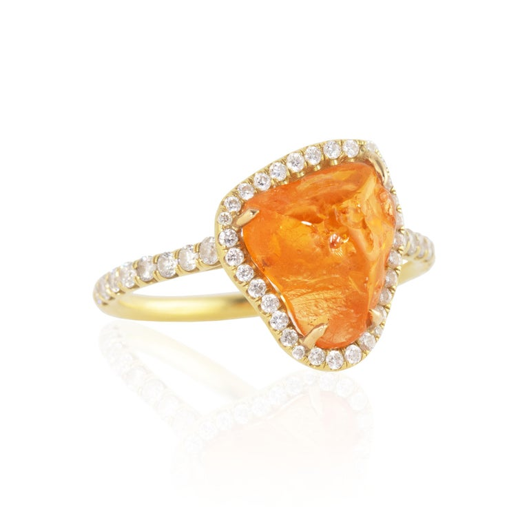 Featuring a large orange, rough cut Fanta Orange Spessartite Garnet center stone and surrounded by diamonds, this ring was inspired by the reflections of the sun on ocean waves.  Featuring a 9.96 carat bright orange rough Spessartite Garnet