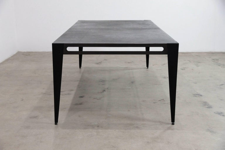 The Icon library table is steel with a bronzed patina. The legs are upholstered in hand stained lamb leather with adjustable feet. The Icon tabletop is upholstered with black saddle leather and black cashmere on the underside. Both the length and
