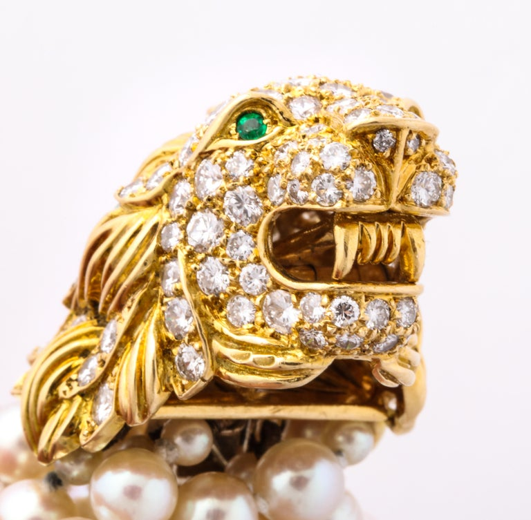 Made by Van Cleef and Arpels 1969, this eye catching pearl bracelet has a stunning lion's head for the clasp with emerald eyes and beautiful diamond work.  Signed Van Cleef and Arpels, serial numbered, and dated.  From Catherine Cariou: