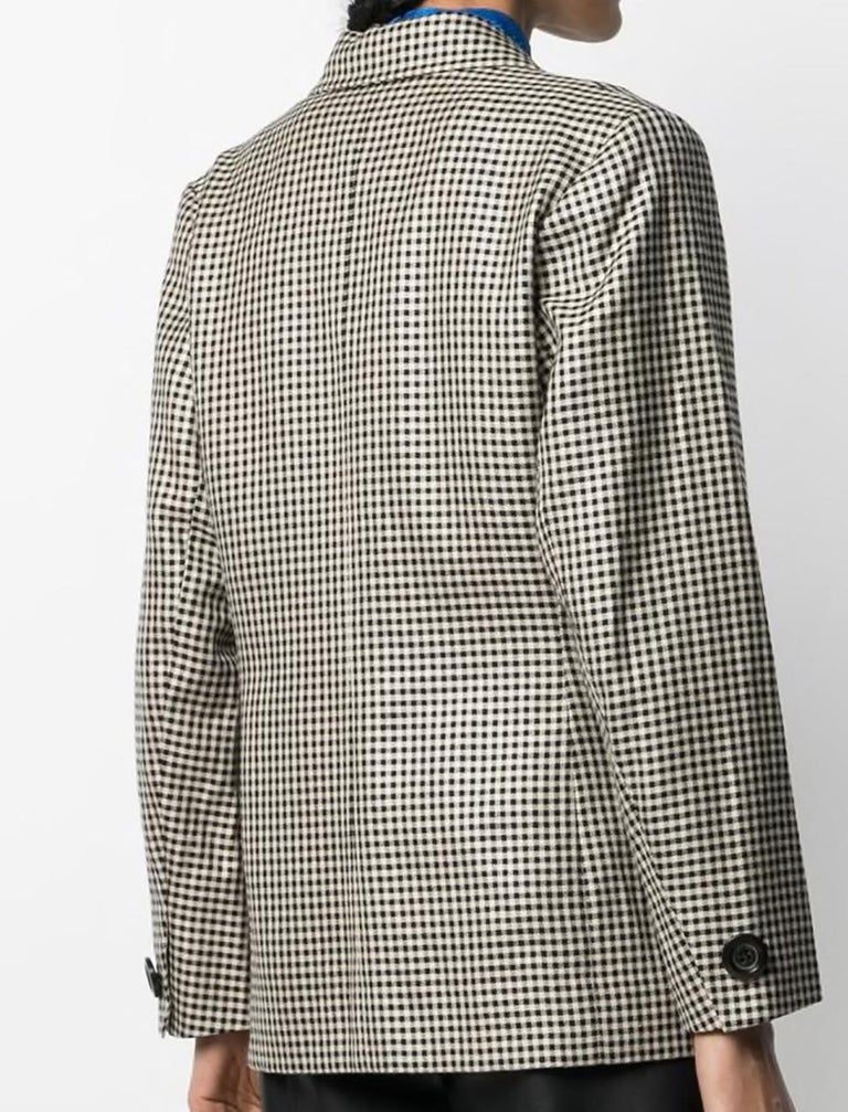 1980s Yves Saint Laurent check single-breasted blazer featuring notched lapel, a black & ivory gingham check pattern, front button fastening, padded shoulders.  Composition: 100% wool Estimated size 38fr/US6 /UK10 In excellent vintage condition.
