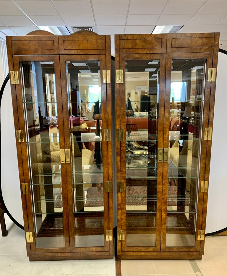 Matching pair of rare and iconic signed mid century burl and glass vitrines from American of Martinsville. Made in the USA, circa 1970's. Come with custom glass shelves and fully electrified. Campaign styling at its best. Features all original brass