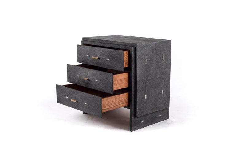 The iconic bedside by R&Y Augousti is one of their first designs. A classic and functional bedside table, with subtle geometry on the beveled drawers. This bedside table is completely inlaid in black shagreen with discreet bronze-patina brass