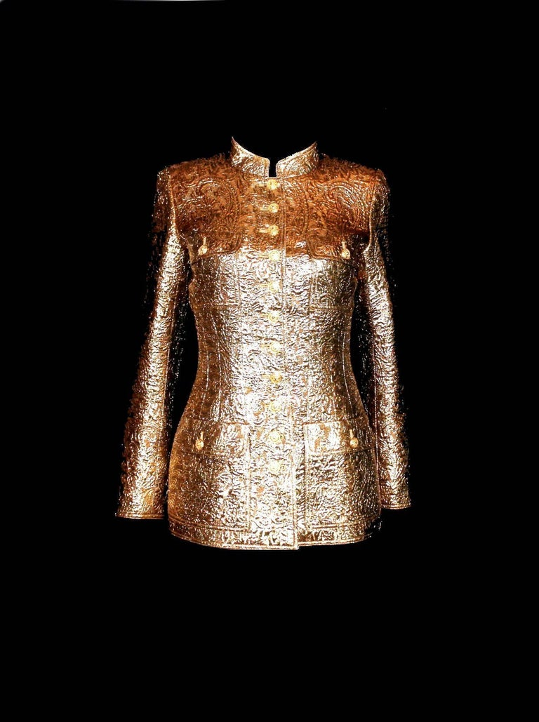 A true icon designed by Karl Lagerfeld for Chanel Golden metallic jacket 3D structure Golden buttons in front and on sleeves with CC logo Fully lined with beige CC logo silk Seen in the Chanel exhibition in the Metropolitan Museum NYC Part of the AD