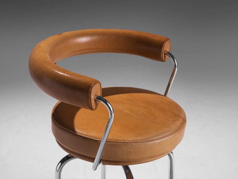 Mid-Century Modern Iconic Charlotte Perriand 'LC7' Swivel Chair in Tubular Steel and Cognac Leather For Sale