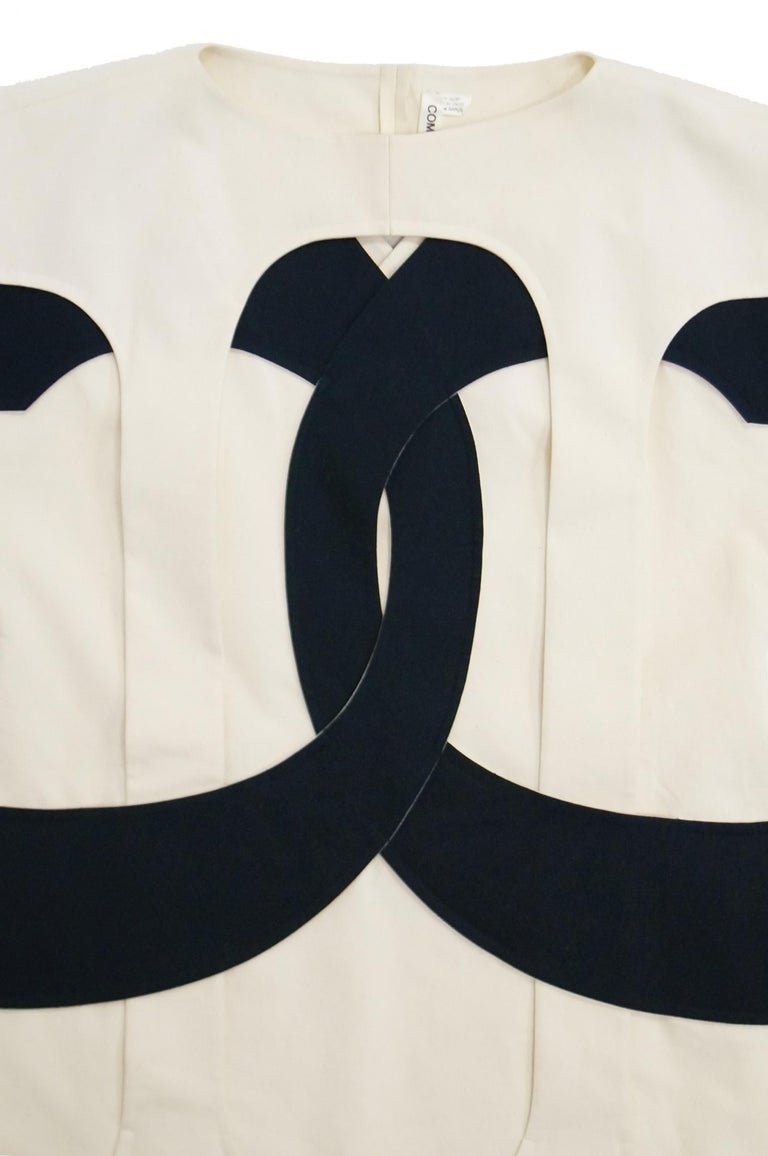 An iconic Rei Kawakubo/Commes des Garcons black and white cotton calico pinafore dress, Spring-Summer, 2014, printed ribbon label, with dramatic black symbol appliquéd and interwoven through the sleeves, attached to the angular side panniers and