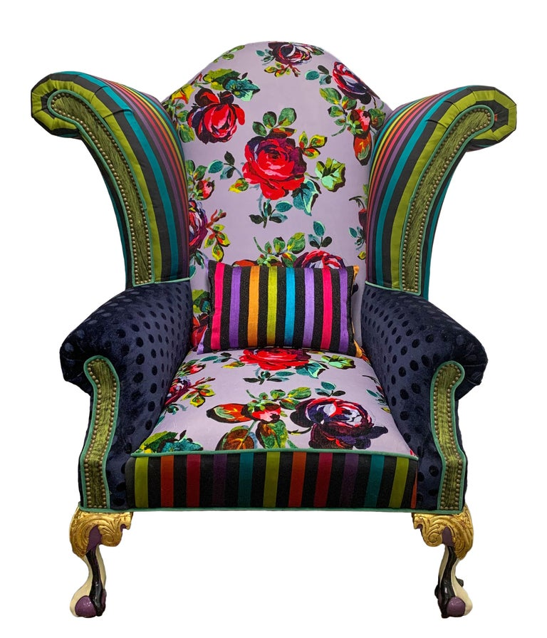 Iconic Mackenzie-Childs monumental armchair in zany eye-popping florals, stripes and dots. Upholstered in luxurious textural fabrics with hand carved claw-foot legs that are gold-leafed and hand painted by their artisans in Aurora, New York.