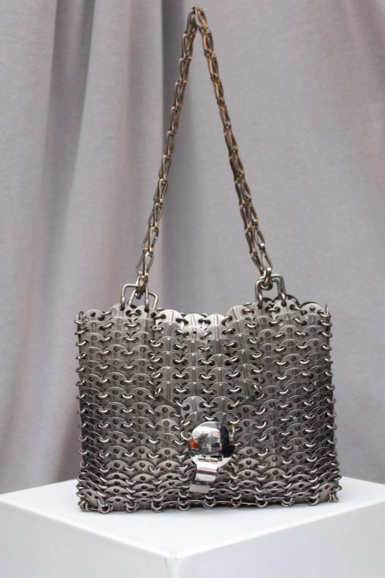 "PACO RABANNE (Made in France) Iconic ""69"" bag comprised of silver-tone perforated chips, typical of the fashion house work in the 1960-1970's. This piece features a flap and is decorated with a cylindrical closure issued in limited numbers at the"