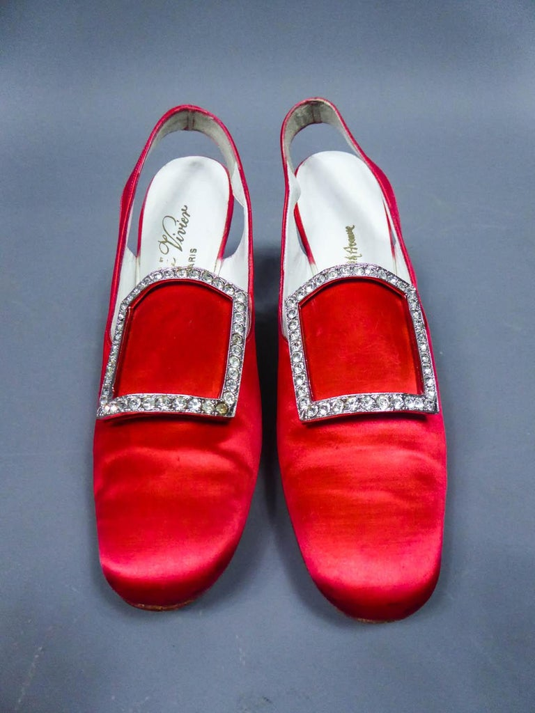 Circa 1970 France for the American market  Iconique Pair of Roger Vivier pumps for the American luxury market from the 70s. Fully covered with vermilion red silk satin and lined with white leather. Rounded ends decorated with a silver buckle covered