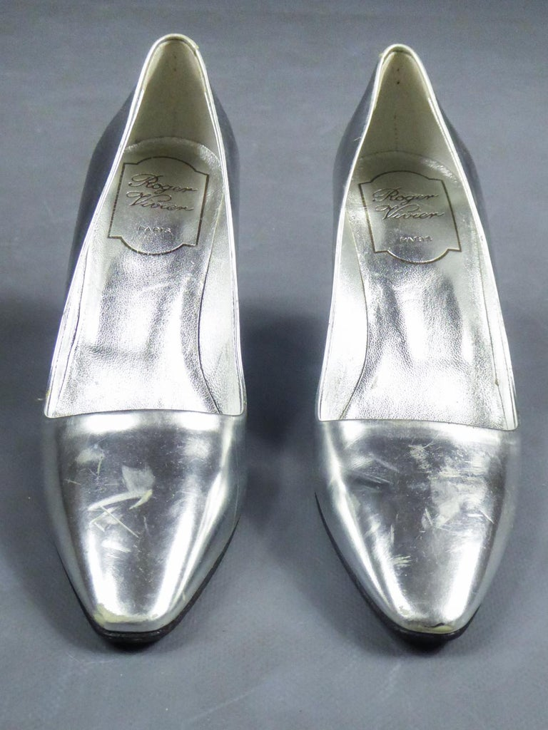 Circa 1980/1990 France/Italy  Iconic Pair of collector'spumps with Virgule heel by Roger Vivier dating from the 1980s. Silver and waxed leather with metallic comma heel and Roger Vivier Paris logo on the sole. Some easily polishable scratches on