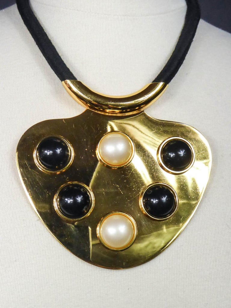 Circa 1970 Paris France  Imposing and iconic pendant necklace by Lanvin from the early 1970s of the Space Age period. Large crew-neck medallion in shiny golden brass in the shape of drop. Cabochons of large half beads in black and pearly bakelite,
