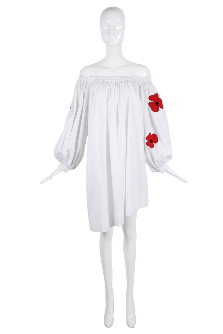 Iconic Yves Saint Laurent white cotton off the shoulder day dress with an asymmetric hem and poppy appliqués at sleeves. Features oversized 3/4 balloon sleeves with gathered elastic cuffs and hidden pockets at either side. In excellent condition/