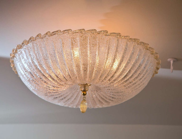 Large shimmery pin cushion shaped ceiling fixture with a lightly gold blown rim, disk and tassel. When illuminated it takes on a beautiful icy effect. This fixture will be made install ready with unlacquered brass hardware to match the brass detail