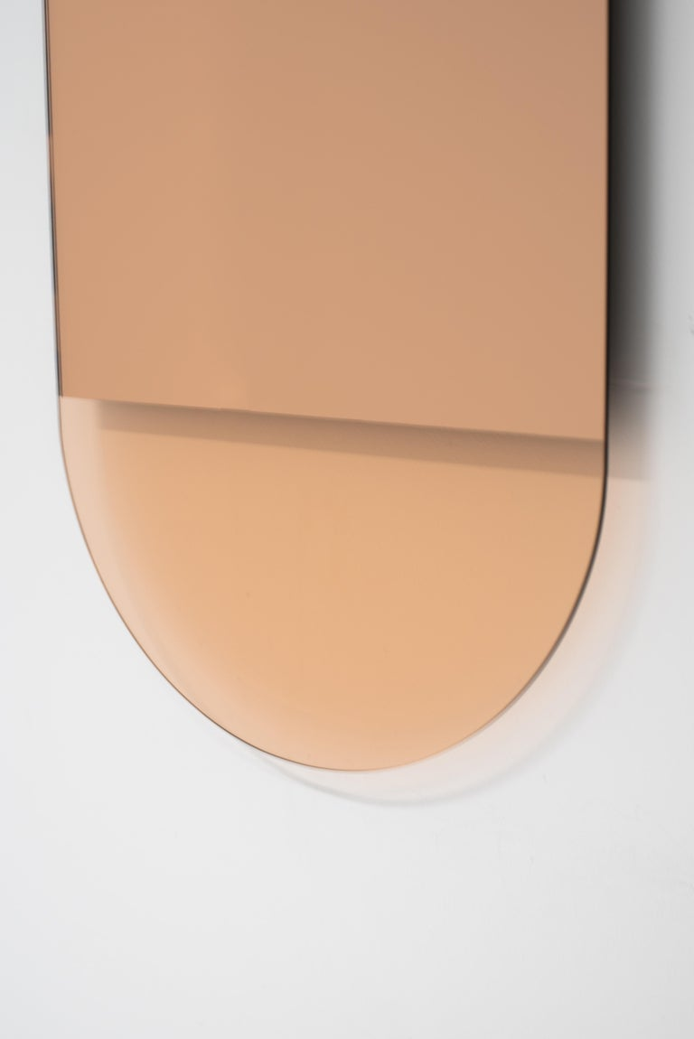 The IDA No. 3 mirror by Ben and Aja Blanc, pairs a Minimalist form with mirror removal to create formal and tonal shifts in this vertical mirror. The warm rose gold colors come from peach mirror and glass creating piece that is both stunning and