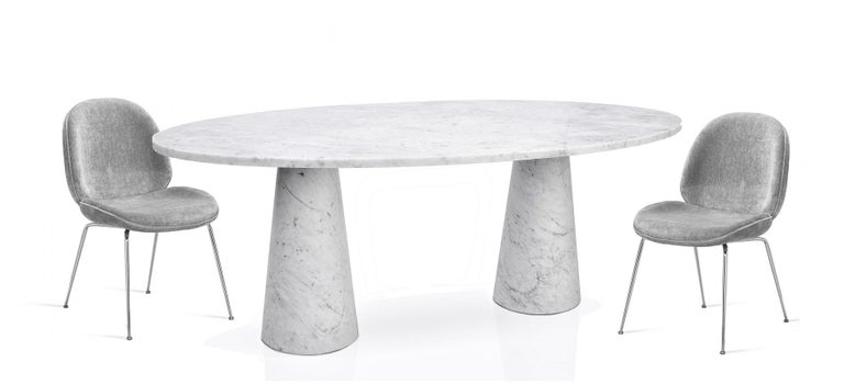 Contemporary oval dining or conference table made out of Carrara marble top and base.  Christophe Pillet who has won international acclaim for the spectrum and quality of his creations, designed the simplest most elegant table that fits equally in