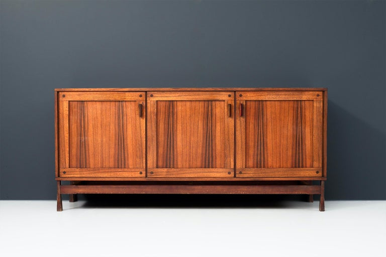 This sturdy three-door Italian credenza is in very good condition and has well balanced proportions. The rosewood top, doors and sides have dark, dynamic, almost dancing flames. The door handles and drawer openings are geometrical shaped and