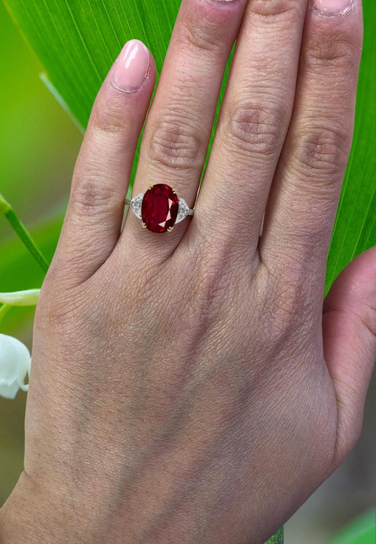 An exquisite and substancial 4.75 carat oval ruby diamond ring  The main stone has an incredible color very bright and red! much more beautiful in person!  the side diamonds are very pure and white  The ring has been handmade and is set in 18 carats