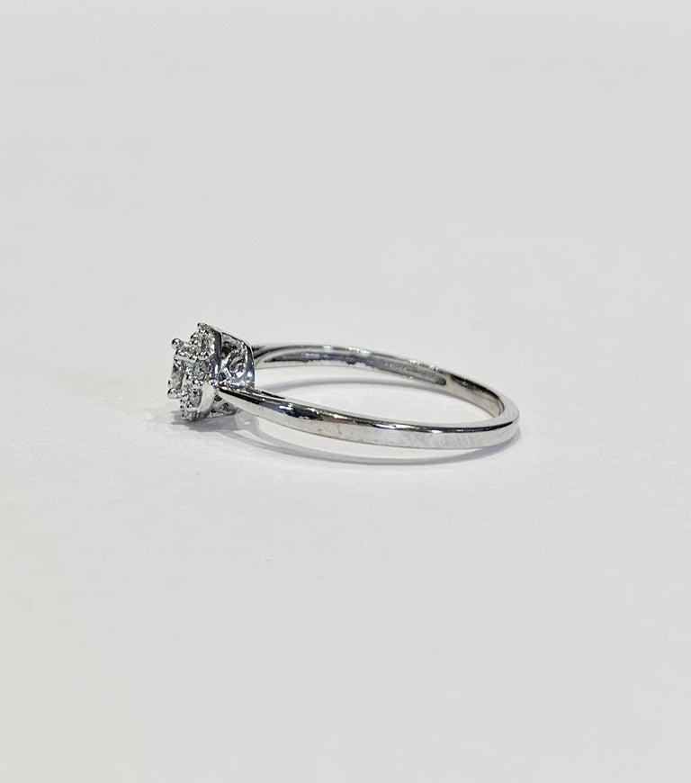 This is a very pretty and delicate cluster ring that has amazing scintillation and also gives the illusion of having a bigger centre stone that is actually has.    The ring is made up of a round brilliant cut centre stone of approximately  .10ct