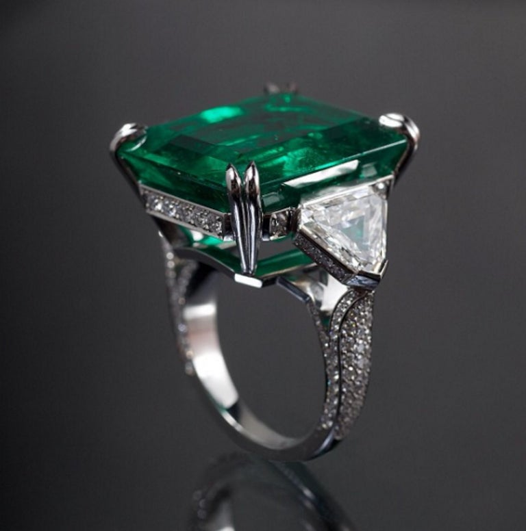 This spectacular ring has inside an emerald top in color, high luster and few minimum inclusions. The ring has been designed and handmade in Italy by our expert goldsmith from Valenza Po.  This ring has two colorless and bright trillions plus a