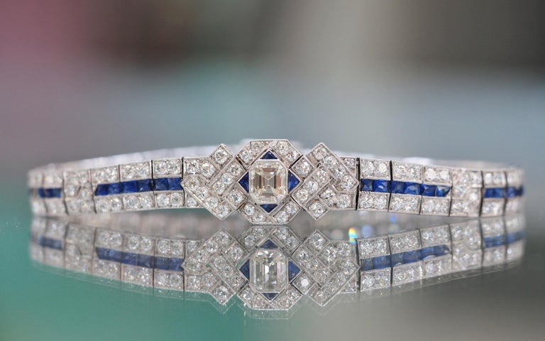 This Art Deco Platinum Diamond and Sapphire Bracelet is absolutely magnificent. It has a 1.00 carat Emerald cut diamond center that is  H-I in color and  VS1 in Clarity. This bracelet includes 4.92 cartas total weight of 164 natural round brilliant