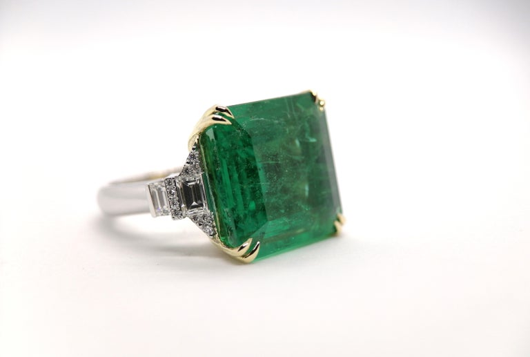 An extraordinary fine XL size 100% natural emerald set in an 18k white and yellow gold mounting with pure natural trapezoid and round brilliant cut diamonds. Consider the pictures were taken with Macro lense that shows the inclusions much more than