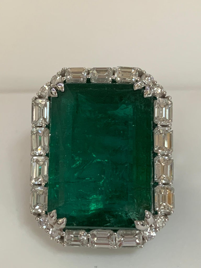 Natural Certified 23.98 Carat Emerald and 5.38 Carat white diamonds set in 18 Karat white gold is one of a kind handcrafted Ring. The ring is size 7 and can be resized if needed.
