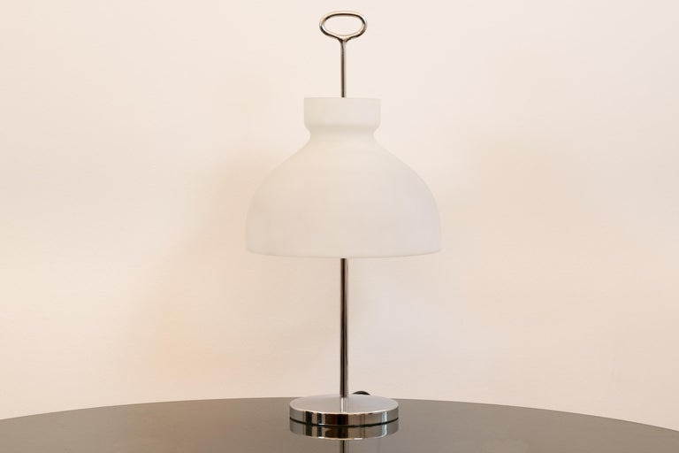 Table lamp model Arenzano, designed by Ignazio Gardella and produced by Azucena in 1956. This beautiful lamp has a chrome-plated brass structure, and satin opaline glass lampshade.
