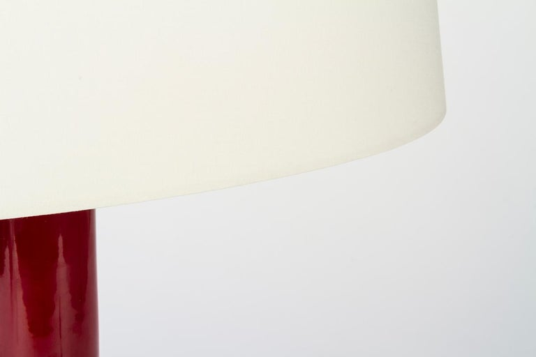 Ikonica, table lamp with body and base made of dark red, glazed ceramic from the famous ceramic district of Bassano del Grappa; lampshade made of cream-white fabric. The warm glaze of the ceramic and the oval lampshade make this lamp designed by