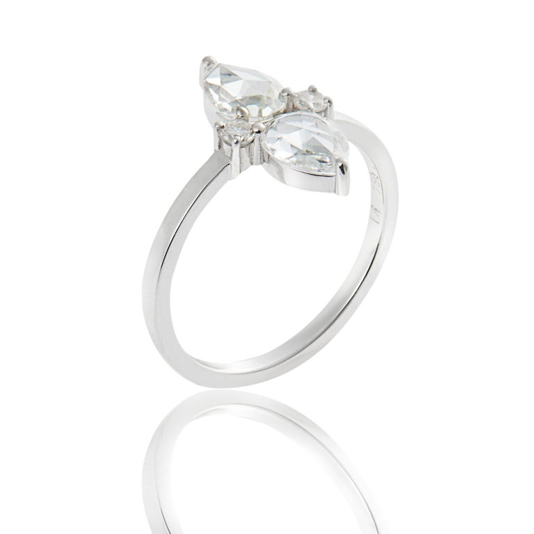 Handcrafted from 18k white gold, this stunning diamond ring features two prong-set, pear-shaped rosecut diamonds embellished with two smaller brilliant cut diamonds.
