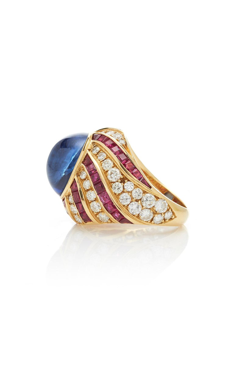 A beautiful ring of vortex design in 18kt yellow gold showcasing a cabochon ceylon sapphire (8 cts), square cut rubies and brilliant cut diamonds. Made in Italy by historical Northern Italian jeweler Illario, circa 1975.