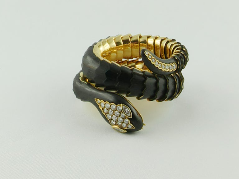 This Stylish extendable Illario Ebony Gold and Diamonds Bracelet wraps around the wrist twice depicting a scaled snake artistically rendered thanks to Wood scales  The Bracelet is excepionally crafted in 18 karat Yellow Gold with pavé Diamond on the