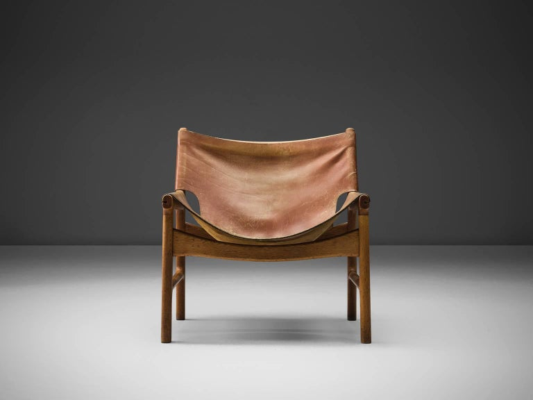 Illum Wikkelsø for Mikael Laursen, easy chair model 103, leather and oak, Denmark, 1960s.  This easy chair is a design by Illum Wikkelsø but produced by master-carver and cabinetmaker Mikael Laursen. The leather is attached to the frame of the