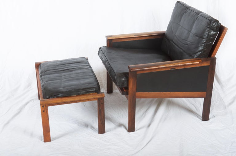 Illum Wikkelsø. Solid hardwood armchair, upholstered in black leather. Related stool H. 35 cm. Manufactured by N. Eilersen, model Capella. Traces of age and wear, including among other things.