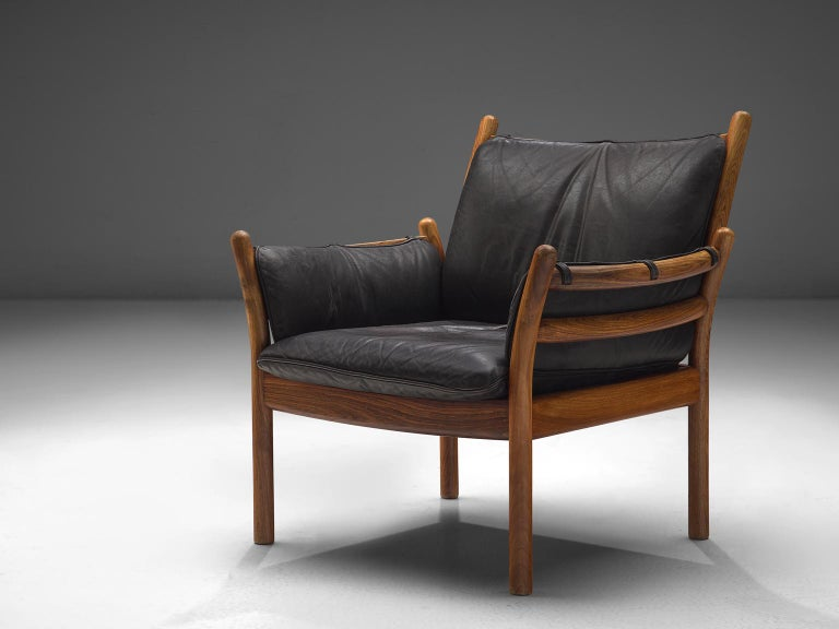 Illum Wikkelsø by CFC Silkeborg, 'Genius' chair, leather and rosewood, Denmark, 1950s.  This chair is made out of solid rosewood and features a cognac leather cushion on both seat and back. The chair is created as a sort of slatted rosewood