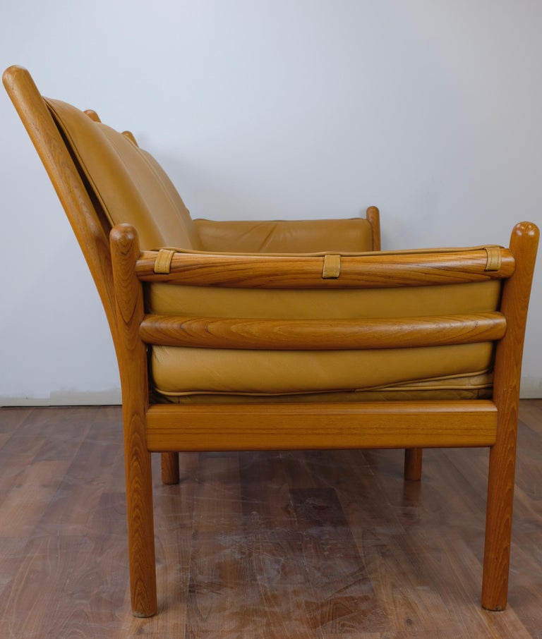One 'Genius' loveseat designed by Illum Wikkelsø and made in Denmark by CF Christensen Silkeborg.  The frame is constructed of solid teak. Cognac leather seat cushions are loose while back and arm cushions are secured to the frame with straps and