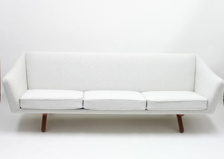 Three seater sofa, model ML-140, designed by Illum Wikkelsø for A/S Michael Laursen. An all Danish collaboration. Newly upholstered in an off-white fabric that sits on a teak base with A-shaped legs. Very good condition with minimal ware.