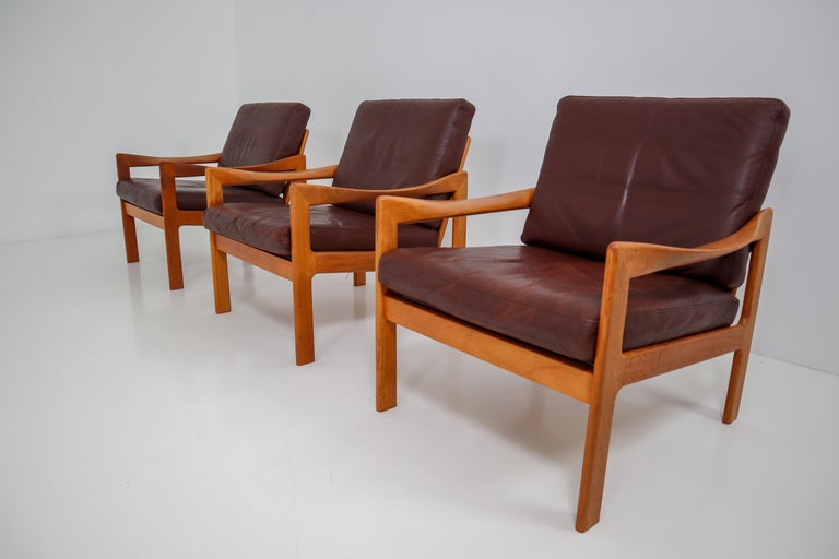 A teak armchair designed by Illum Wikkelsø and produced by Eilersen, Denmark, circa 1960. This beautiful midcentury Danish armchair has wonderfully twisted armrests and original leather upholstery with minor signs of usage and patina. A very