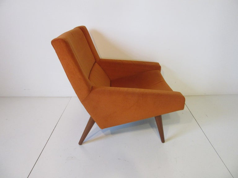 A well crafted upholstered lounge chair in a soft orange fabric with conical solid teak wood legs and having an interesting ergonomically designed shape for comfort. Purchased by the original owners in Denmark and lovingly cared for until their