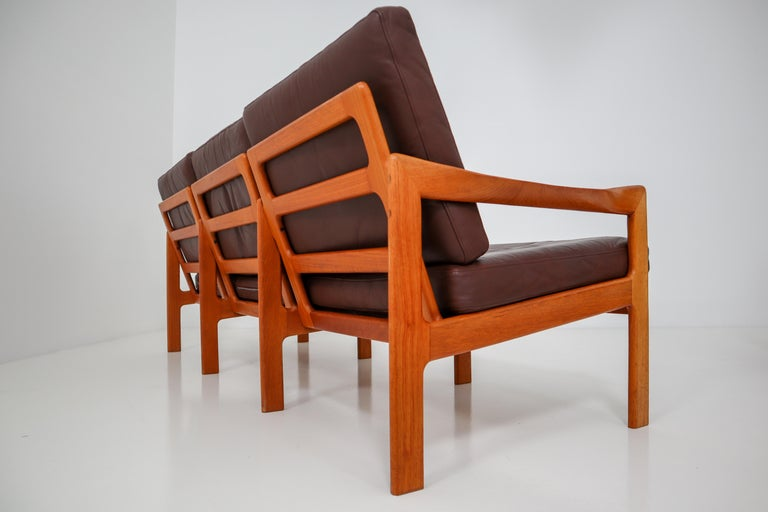 A three-seat teak sofa designed by Illum Wikkelsø and produced by Eilersen, Denmark, circa 1960. This beautiful midcentury Danish sofa has wonderfully twisted armrests and original leather upholstery with minor signs of usage and patina. A very