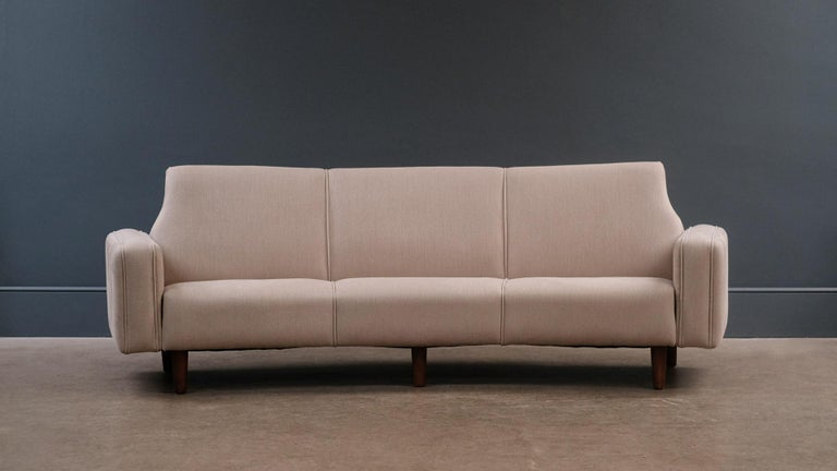 A rare and beautiful curved sofa designed by Illum Wikkeslo for Aarhus Mobelfabrik, Denmark, 1958. This example fully refurbished and reupholstered in heavy linen fabric by Kirkby.