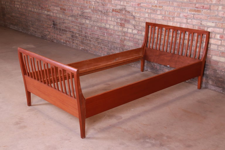 A gorgeous midcentury Danish modern sculpted teak twin size bed frame  By Illums Bolighus  Denmark, circa 1950s  Measures: 41.5