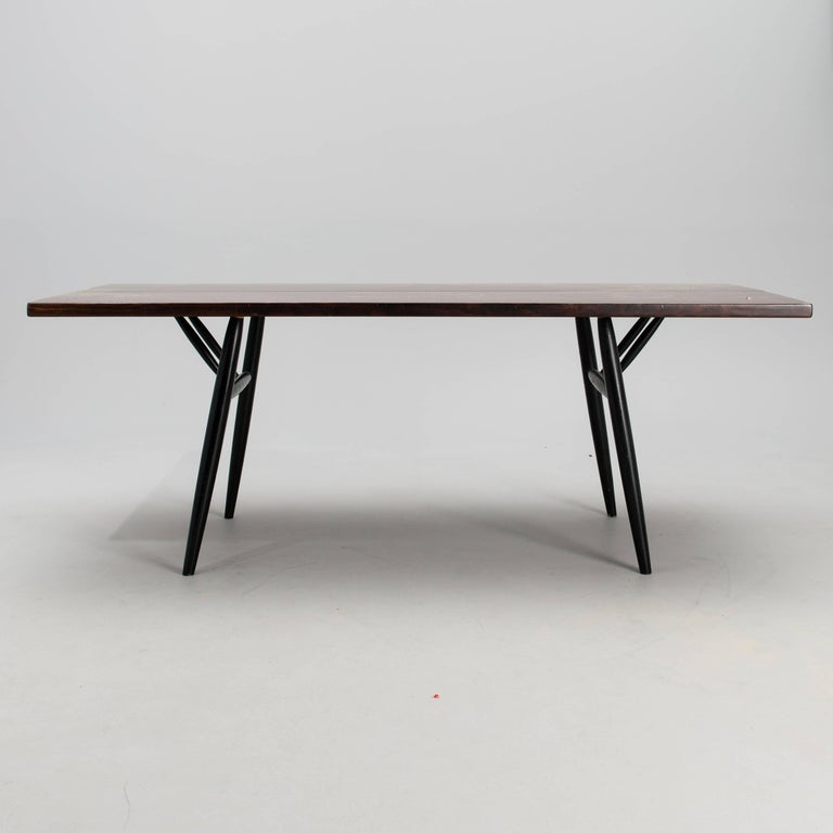 Original 'Pirkka' large table designed by Finnish interior architect Ilmari Tapiovaara and manufactured by Laukaan Puu in Finland, circa 1955-1960. Top in dark pine and legs in black-lacquered birch.