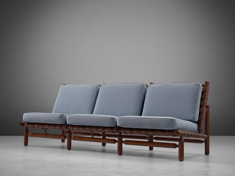 Sofa and lounge chair, in teak and leather, by Ilmari Tapiovaara for Esposizione La Permanente Mobili manufactured by Paolo Arnaboldi, Italy, 1957.   This rare three-seat sofa and lounge chair by Finnish designer Ilmari Tapiovaara (1914-1999).