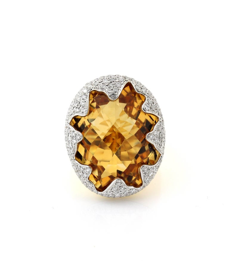 18K Yellow and White Gold Ring with Imperial Citrine Center and Diamonds  Center Citrine is gorgeous in color, has a slight color change aspect. The carat weight is unknown but we are estimating around 20 carat's. The face of the ring is 1.1 inch x
