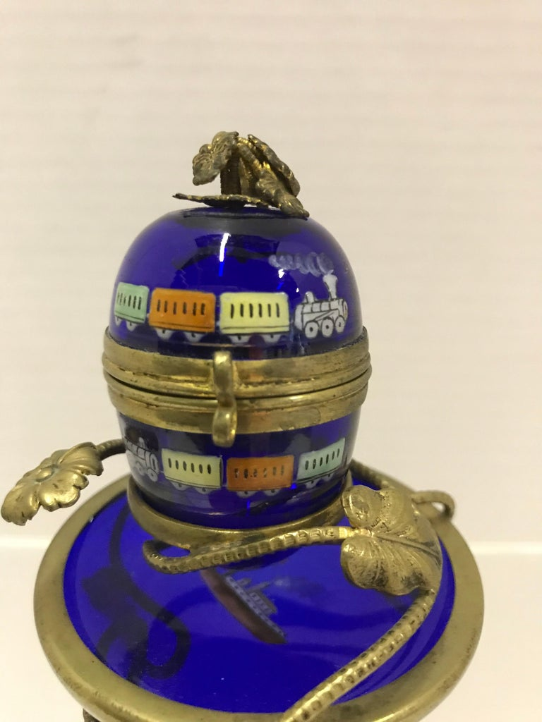 Attributed to the Imperial Glassworks of Saint Petersburg, Russia, an early 1900 cobalt blue glass Egg with gilt stand. Enameled paint decoration with turn of the century trains and steam ship. All this accented with a brass d'ore stand and mounts