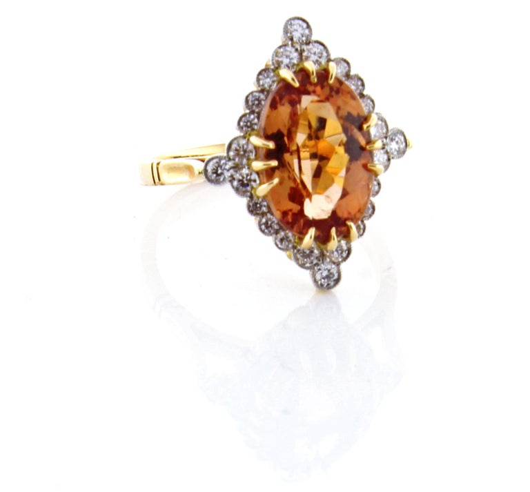 From the master ring makers of Pampillonia, an Imperial topaz and diamond ring. The ring boast anovel Topaz weighing 4.62 carat and 24 diamonds weighing .34 carats. The ring is entirely handmade  from 18 karat peach gold and platinum overlay. Size 6