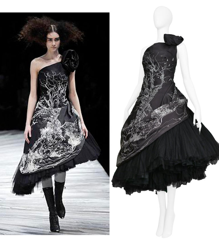 We are excited to offer an important vintage Alexander McQueen runway gown featuring a black satin taffeta asymmetrical strapless dress over attached layers of black heavy tulle, a black rosette, single strap, and center back zipper. The white