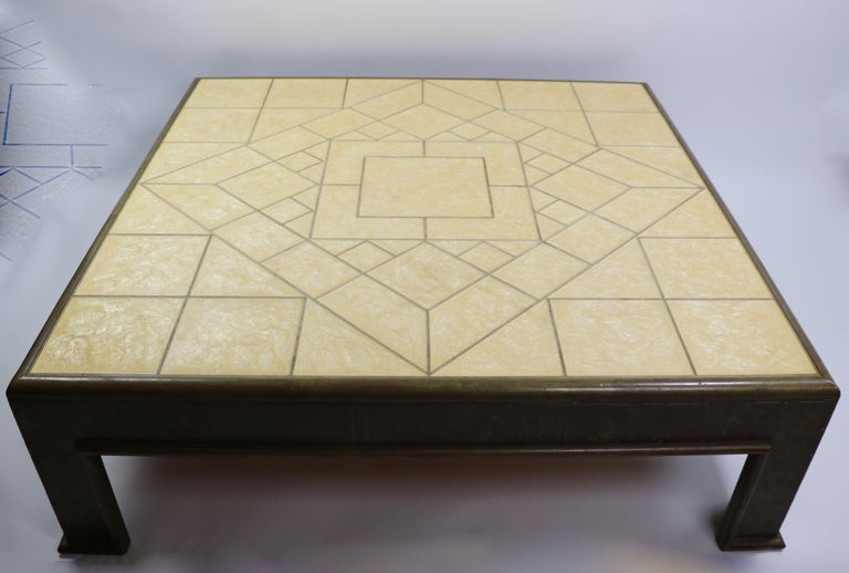 Large and impressive coffee table by recognized master artisan and designer, Rodolfo Dubarry. This example has brass, or bronze, metal legs and frame with a mother of pearl (Madre Perla) and wood inlay top surface. The table exhibits both 1970s