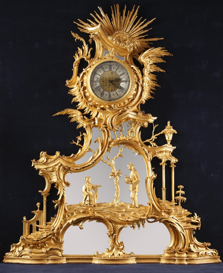 Important clock with a mirror background of Rococo inspiration with a rich sinuous and asymmetrical decoration representing a Chinese couple above a cave, in an environment formed by scrolls, arches and columns. The scene is topped by a winged dial